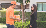 Delivery man in orange is handing packages to a woman - 206369825
