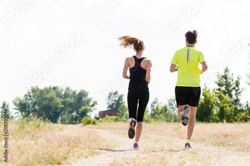 Fotobehang Hardlopen Couple jogging in nature rear view