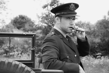 Handsome American WWII GI Army officer in uniform smoking cigar next to Willy Jeep