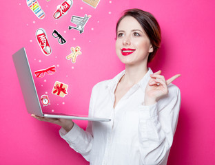 Portrait of young redhead businesswoman with laptop on pink background