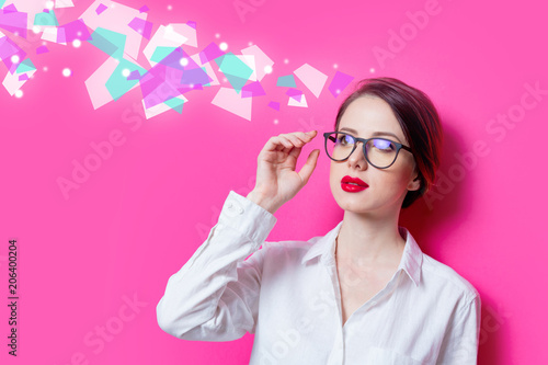 Beautiful redhead businesswoman in white shirt with abstract colored ideas on pink background