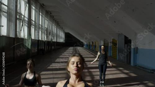 Sticker Tilt down of three sportswomen in fitness clothes jumping rope before camera while training in gym