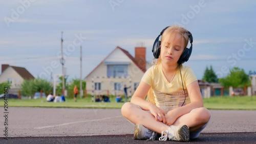 Happy little girl listening music on headphones in the stadium on sunny day.
