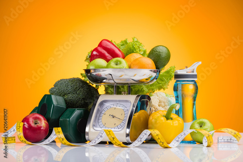 Poster close-up view of fresh fruits and vegetables on scales, sports bottle with water, dumbbells and measuring tape on yellow