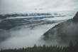 Between layers of clouds, Howe Sound appears from high above
