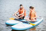 Couple in life vest relaxing on the stand up paddle board doing yoga - 206441445