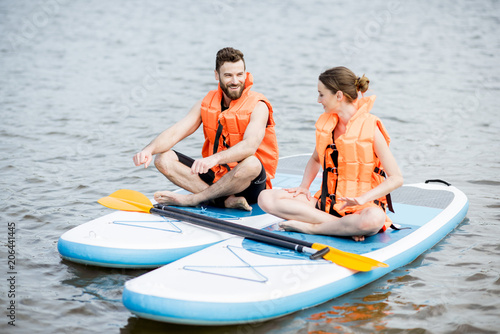 Fototapeta Couple in life vest relaxing on the stand up paddle board doing yoga