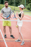 Young couple having fun standing together on the tennis court relaxing after the match outdoors