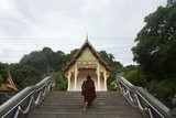Thai monk walking at Wat Tham Khuha Sawan in Phatthalung, Thailand