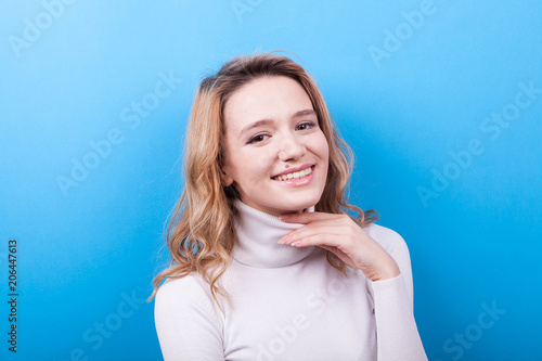 Woman with a big natural smile looking to the camera on blue background in studio photo