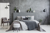 Grey stool in front of bed with blankets and cushions in dark hotel bedroom interior. Real photo - 206459256