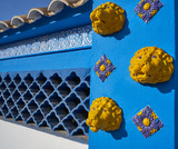 Mediterranean facade in blue with yellow lion tiles and ceramic lattice - 206460472