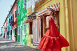 Young fashionable woman in romantic red dress and straw hat, with braid hairstyle, posing near colorful houses in Burano Island, Venice, Italy