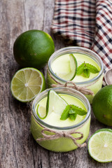 Natural  lime yogurt in a small glass jar on wooden table