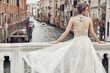 Beautiful bride with tattoo on back, dressed in elegant, luxury ivory dress and updo hairstyle, posing on a bridge over the canal in Venice