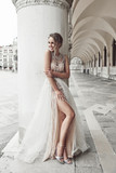Beautiful bride in long elegant, luxury ivory dress and messy updo hairstyle, posing near column in Venice, Italy