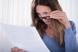 Shocked Woman Looking At Document In Office - 206493463