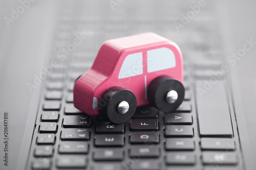 Fridge magnet Wooden car toy on laptop keyboard