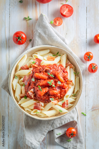 Delicious penne bolognese with bacon and herbs © shaiith