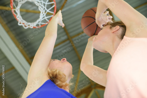 Fotobehang Basketbal Upward view of woman aiming for basketball net