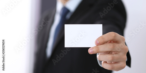 Businessman's hand holding business card with empty space