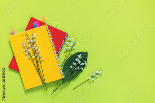 Fotobehang Lelietjes van dalen Lily of the valley and red and yellow notebooks