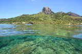 Over Under Shot of a tropical island in Fiji showing the coral reef underwater and a rocky mountain on the island