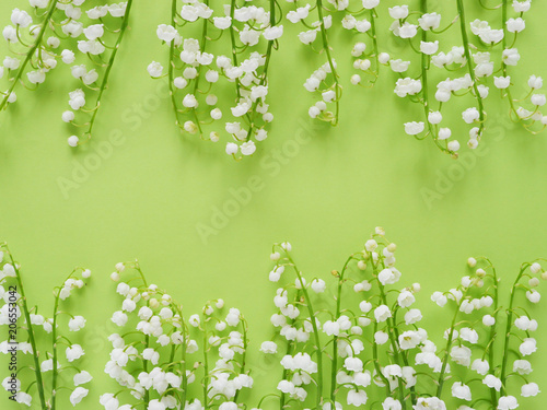 Fotobehang Lelietjes van dalen Romantic gentle flower background, lily of the valley on a green background, top view, flat layout.
