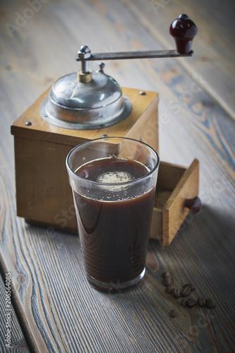 Foto Murales Black coffee with coffee grinder placed