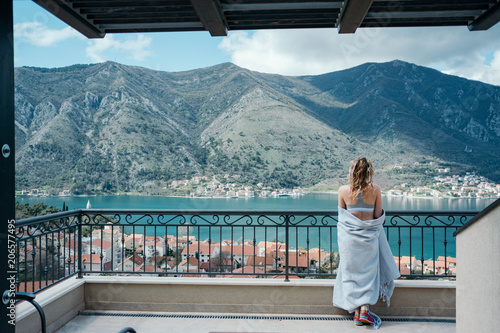 Fotobehang Groen blauw Pretty blonde hair woman enjoys the view of the sea and mountains in the Boka-Kotorsky bay, Montenegro
