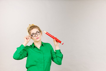 Woman confused thinking, big pencil in hand