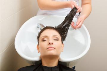 Hairdresser washing her woman customer hair © Voyagerix