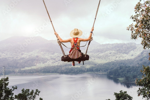 Carefree woman on the swing on a inspiring landscape. © Kar Tr
