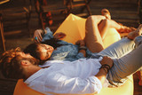 Young couple lying in a lazy bag during the sunset