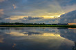 Sunbeams through retreating storm clouds form beautiful reflection in pond