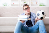Young student trying to balance studying and playing football - 206645899