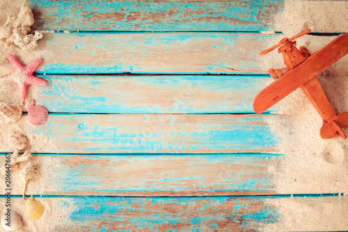 Foto Murales Have a vacation and travel in summer concept - top view of beach sand and toy air plane on wood plank in blue sea paint background.
