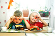 Cheerful children at Breakfast . Brother and sister with sandwiches