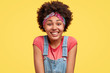 Happy dark skinned young female being in good mood, looks positively at camera, has broad gentle smile, rejoices weekend and free time, dressed in jean overalls, poses against yellow background.