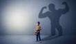 Leinwanddruck Bild - Little waggish boy in an empty room with musclemen shadow behind