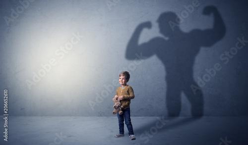 Leinwanddruck Bild Little waggish boy in an empty room with musclemen shadow behind