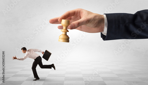 Leinwanddruck Bild Small frail businessman with suitcase running away from big hand with chessman concept