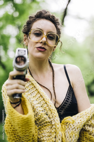 Young woman using an vintage cinema camera in a park