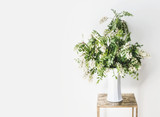 Flowers bunch with blossom of acacia branches in vase at white wall. Simple Interior design and ideas . Still life - 206672448