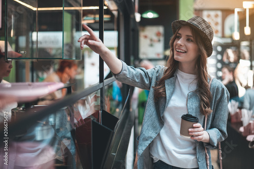Leinwanddruck Bild Smiling young woman is pointing at glass case while standing in cafe. She is wearing stylish hat and holding hot drink