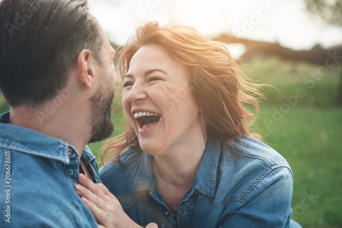 Leinwanddruck Bild Portrait of excited middle-aged woman is laughing from the joke which man telling her. They are relaxing in the nature and hugging