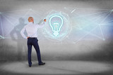 Businessman in front of a wall with bulb lamp idea concept icon on a futuristic interface - 206679869