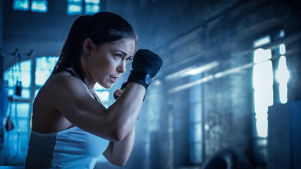 Athletic Woman Trains Her Punches on a Punching Bag that Her Partner/ Trainer Holds. She's Strong and Gorgeous Woman. They Workout in a Gym.