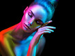 Leinwanddruck Bild - Fashion model woman in colorful bright sparkles and neon lights posing in studio, portrait of beautiful sexy girl. Art design colorful vivid makeup