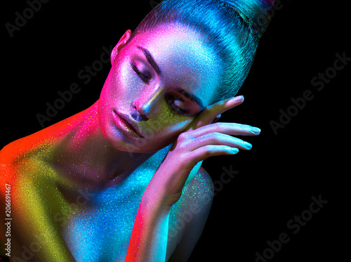 Leinwanddruck Bild Fashion model woman in colorful bright sparkles and neon lights posing in studio, portrait of beautiful sexy girl. Art design colorful vivid makeup